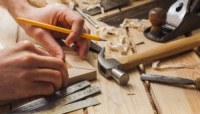 Carpenter Working with Pencil and Hammer